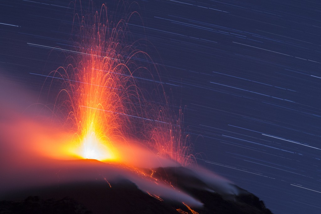 Volcán en erupción con cielo estrellado